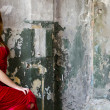 Stock Photo: The beautiful girl in an evening dress against an old wall