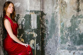 The beautiful girl in an evening dress against an old wall — Stock Photo