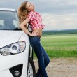 The beautiful girl stands near to white car - Stock Photo