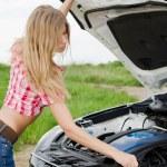 The beautiful girl repairs the car — Stock Photo