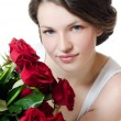 The beautiful girl with a bouquet of red roses — Stock Photo #11876159