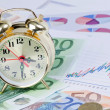 Foto Stock: Alarm clock for euro banknotes as background
