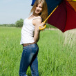 Beautiful girl with a multi-coloured umbrella — Stockfoto #11876549