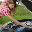 The beautiful girl repairs the car - Stock Photo