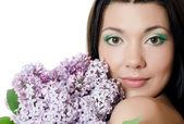 Schöne frau mit frühlingsblumen von einem flieder. hautpflege — Stockfoto