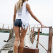 The beautiful young woman with a suitcase at a pier — Stock Photo