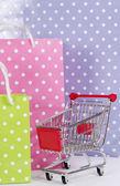 Koszyk na zakupy i torby na białym tle — Zdjęcie stockowe