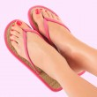 Female legs in pink sandals on pink background — Stock Photo #11337533