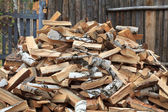 Pile of firewood against old wooden fence — Stock Photo