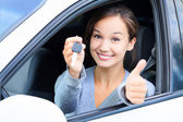 Happy girl in a car showing a key and thumb up gesture — Stock Photo