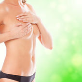 Female controlling breast for cancer, green blurred background. — Stock Photo