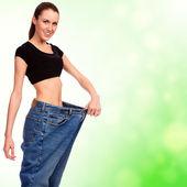 Joven atractiva muestra su enorme par de pantalones vaqueros viejos — Foto de Stock