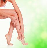 Female legs on green blurred background — Stock Photo