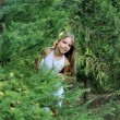 Girl looking out from behind tree — Stock Photo