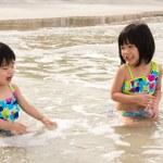 Children enjoy waves on beach — Stock Photo #12064849