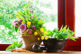 Sack with bouquet of healing herbs and flowers, mortar and pestle on windowsill — Stockfoto