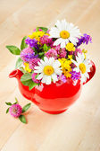 Red teapot with bouquet of healing herbs and flowers — Stock Photo