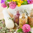 Different healing herbs in glass bottles, flowers bouquet in mort — Stock Photo #11094614