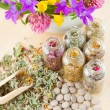 Different healing herbs in glass bottles, flowers bouquet in mort — Stock Photo #11094635