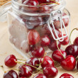 Cherries in glass jar on kitchen table - Stock Photo