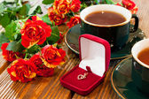 Gold jewelry, cups of tea and roses bouquet — Stock Photo
