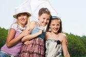 Three happy young girl friends under umbrella — Φωτογραφία Αρχείου