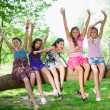 Beautiful happy girls sitting on a tree trunk in park — Stock Photo