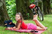 Biker girl relaxing in the park — Stock Photo