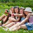 Beautiful girls taking picture on grass in city park outdoors — Stock Photo #12148811