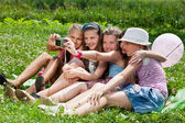 Beautiful girls taking picture on grass in city park outdoors — Stock Photo