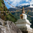 Buddhist stupe or chorten with prayer flags in Himalayas — Stock Photo