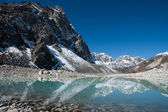 Mountain peaks and reflection in Sacred Gokyo Lake in Himalayas — Stock Photo