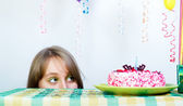 Holiday. A girl looks out from under the table — Stock Photo