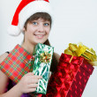 Attractive girl in a Christmas hat with gift boxes — Stock Photo
