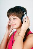 Teenage girl listening to music on headphones — Stock Photo
