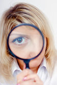 Woman looking through a magnifying glass — Stok fotoğraf