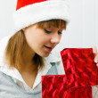 Attractive girl opens a Christmas present — Stock Photo