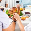 Family members giving thanks to God at festive table — Stock Photo