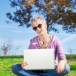 Young woman with laptop on grass — Stock Photo #11932458