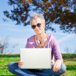 Young woman with laptop sitting on grass — Stock Photo #11932470