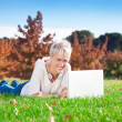 Smiling girl using laptop outdoors. — Stock Photo #11932480
