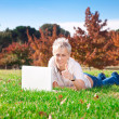 Stock Photo: Smiling girl using laptop outdoors
