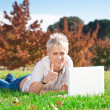 Smiling girl using laptop outdoors — Stok fotoğraf