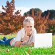 souriante jeune fille à l'aide d'ordinateur portable à l'extérieur — Photo
