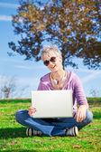 Young woman with laptop on grass — Stock Photo