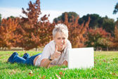 Smiling girl using laptop outdoors — Stock Photo