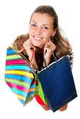 Portrait of young happy woman in dress with colorful shopping ba — Stock Photo