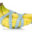 Bananas wrapped with measuring tape — Stock Photo