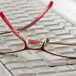 Stock Photo: Glasses on computer keyboard