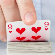 Hand revealing nine of hearts — Stockfoto